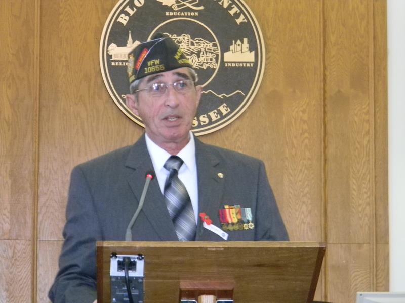 Man in grey suit with lapel medals and veteran's hat stands at wooden podium speaking